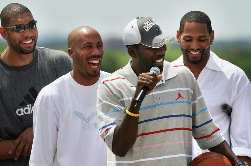 Tim Duncan, left, Bruce Bowen, left center, and Robert Horry, right, laugh as Michael Finley, center