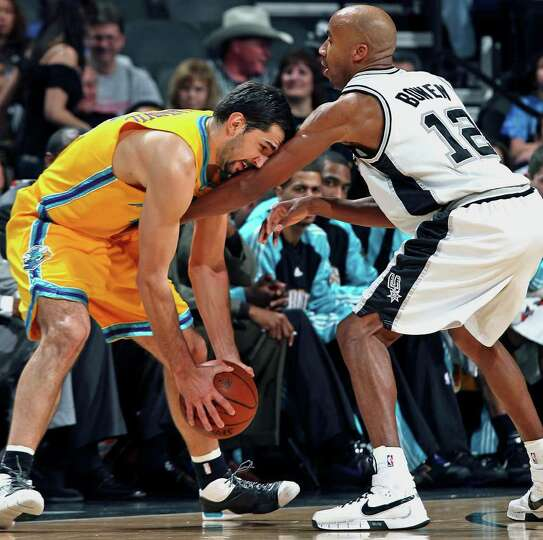 The Spur's Bruce Bowen applies defensive pressure to Hornets forward Peja Stojakovic in the first ha