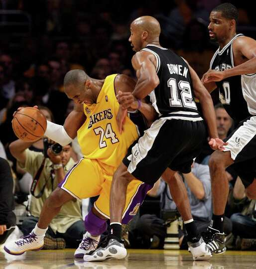 Under the pressure of a double team of San Antonio Spurs Bruce Bowen and Kurt Thomas, Los Angeles La