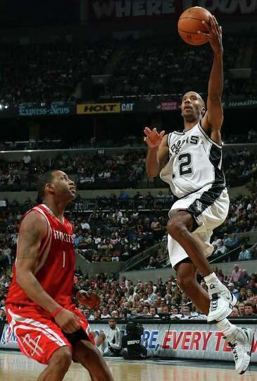 Spurs' Bruce Bowen shoots over Rockets' Tracy McGrady during second half action Sunday March 30, 200