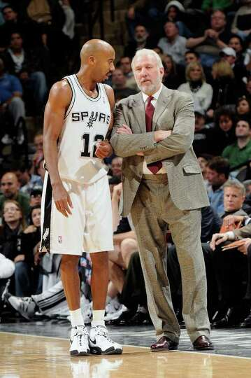 Bruce Bowen #12 of the San Antonio Spurs talks to Head Coach Gregg Popovich during the game against