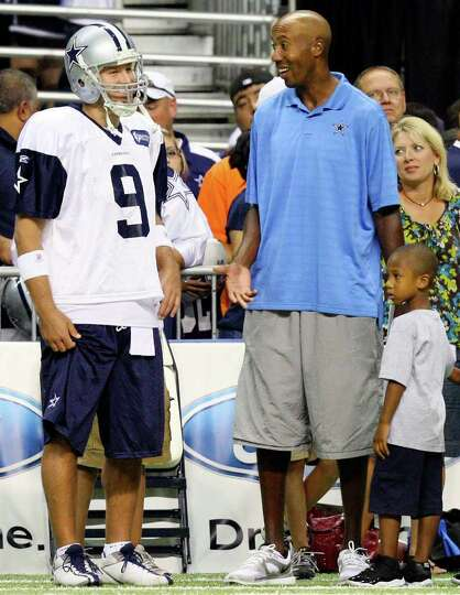 Dallas Cowboys' Tony Romo talks with former Spurs player Bruce Bowen during afternoon practice at Co