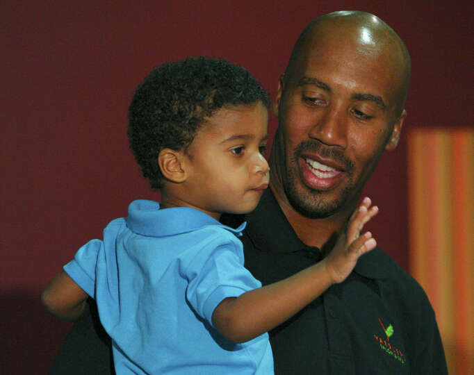 Former Spurs' player Bruce Bowen holds his son Ojani Bowen, 3, prior to a press conference where