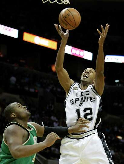 Spurs' Bruce Bowen (12) reacts while grabbing a rebound against the Boston Celtics' Glen Davis (11)