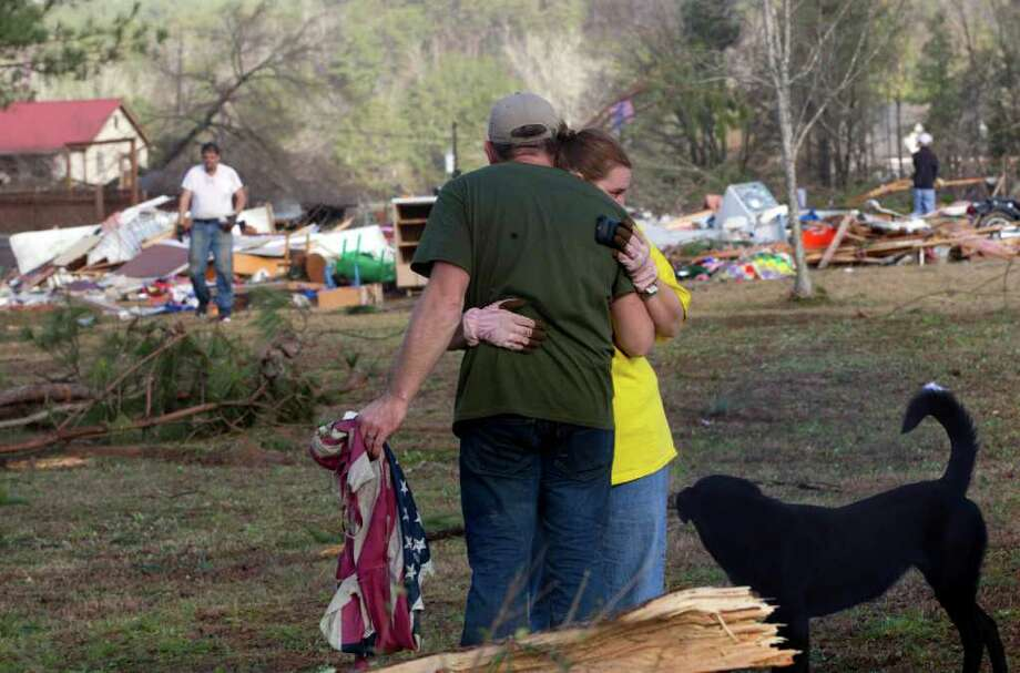 Russ Butler hugs his wife, Amber, as the cleanup process gets under way Monday in Oak Grove, Ala.At least one person was killed when a suspected tornado swept through the area. Photo: Dave Martin / AP