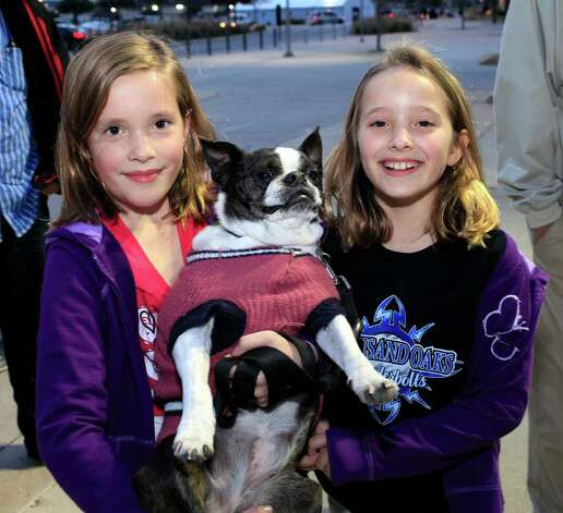 Nine-year-old twins Chloe and Zoe Skeistaitis, with Boston terrier Zukie, join fellow hockey fans bringing their dogs to The Rampage Pucks & Paws Night at the AT&T Center, Saturday, January 21, 2012. Dog rescue and adoption groups from throughout the region were also on hand encouraging dog adoption. Photo: J. MICHAEL SHORT, SPECIAL TO THE EXPRESS-NEWS / THE SAN ANTONIO EXPRESS-NEWS