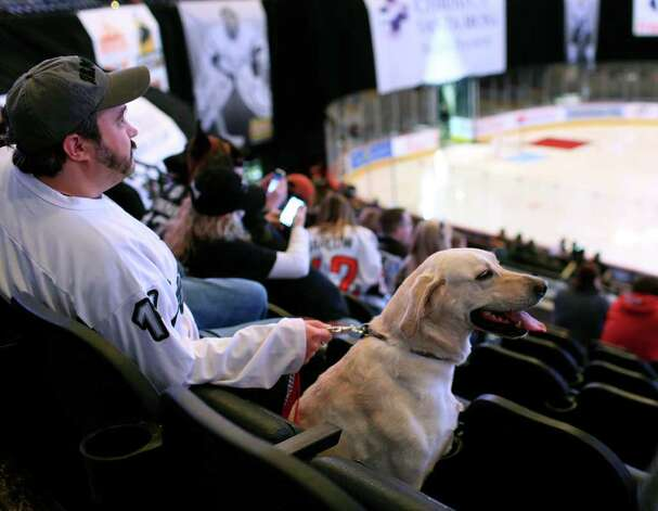 Paul Christiansen and Daisy await the start of the match as hockey fans bring their dogs to The Rampage Pucks & Paws Night at the AT&T Center, Saturday, January 21, 2012. Dog rescue and adoption groups from throughout the region were also on hand encouraging dog adoption. Photo: J. MICHAEL SHORT, SPECIAL TO THE EXPRESS-NEWS / THE SAN ANTONIO EXPRESS-NEWS