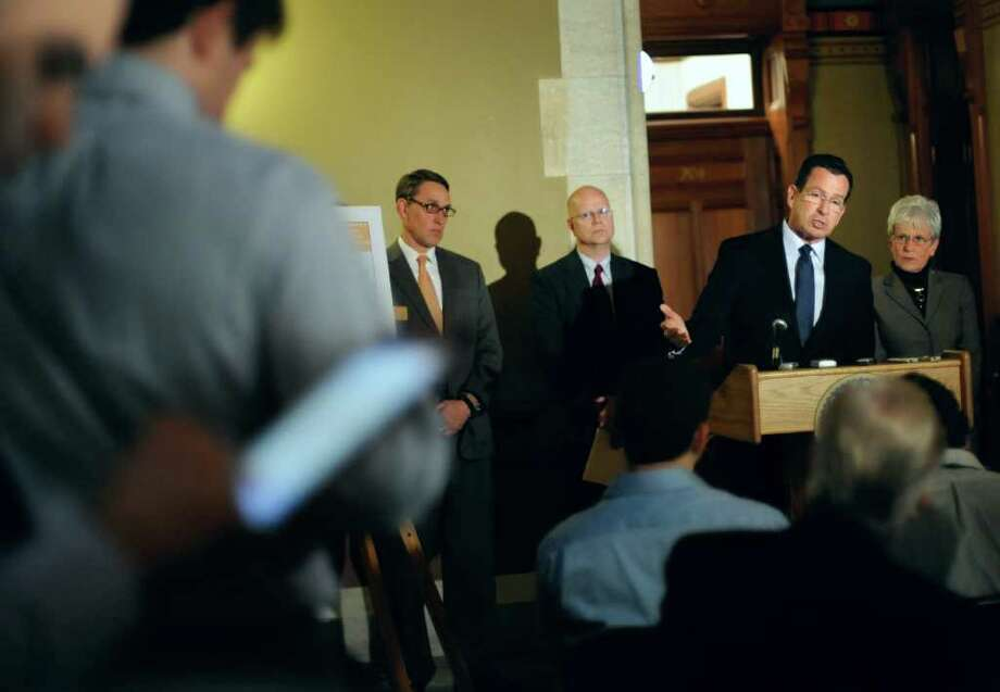 Gov. Dannel P. Malloy, at podium, speaks to the media at the Capitol as budget chief Ben Barnes, left,  state Comptroller Kevin Lembo, second from left, and Lt. Gov. Nancy Wyman, right, look on in Hartford, Conn., Monday, Jan. 23, 2012. Malloy proposed a 20-year plan that will speed up state payments to Connecticut's underfunded state employee pension system. The state's pension fund is currently funded at less than 48 percent, ranking it among the worst in the nation. (AP Photo/Jessica Hill) Photo: Jessica Hill, Associated Press / AP2012