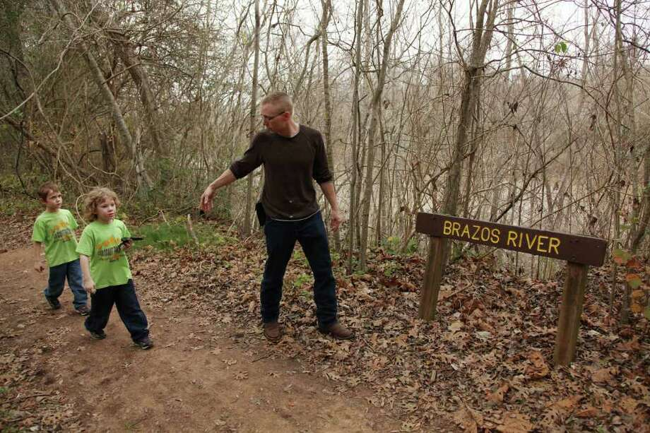 "Jordan Smith, 5, and Brycen Smith, 6, follow Brett Neiditk along Red Buckeye Trail at Brazos Bend State Park at the Brazos River in Needville. Some people fear it could ""turn into a ditch"" if all future demands for water are met. Photo: Mayra Beltran / © 2012 Houston Chronicle"