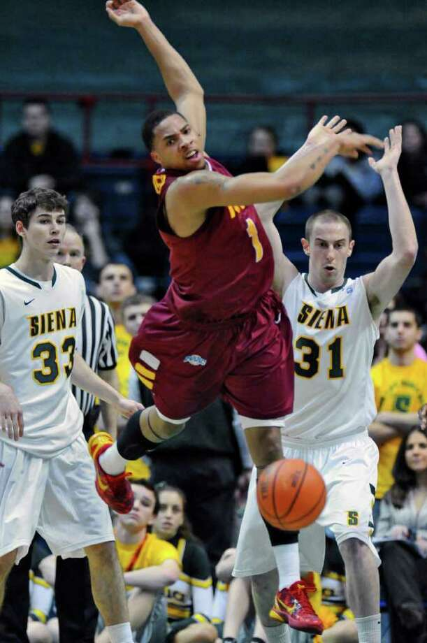 Iona's Mike Glover, center, loses the ball while defended by Siena's Rob Poole, left, and Owen Wignot, right,  during the first half of Siena's 65-62 upset victory at the Times Union Center on Monday night Jan. 23, 2012 in Albany, NY.   (Philip Kamrass / Times Union ) Photo: Philip Kamrass / 00015373I