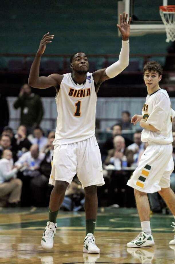 Siena's OD Anosike, left, and Rob Poole, right, look to the bench during the closing moments of their 65-62 upset victory over Iona at the Times Union Center on Monday night Jan. 23, 2012 in Albany, NY.   (Philip Kamrass / Times Union ) Photo: Philip Kamrass / 00015373I