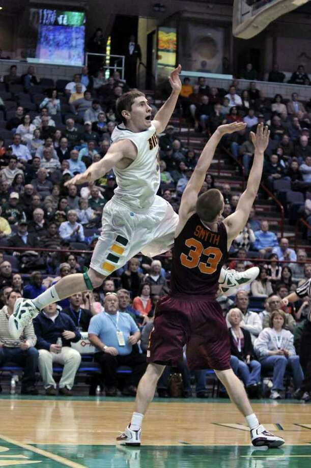 Siena's Kyle Downey jumps over Iona's Kyle Smyth during the second half of Siena's 65-62 upset victory  at the Times Union Center on Monday night Jan. 23, 2012 in Albany, NY.   (Philip Kamrass / Times Union ) Photo: Philip Kamrass / 00015373I