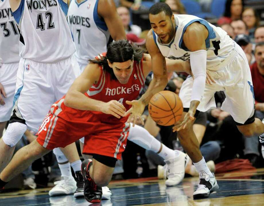 The Timberwolves' Wayne Ellington, right, and the Rockets' Luis Scola scramble to corral a loose ball in the first half Monday. Scola's hustle helped him to add 15 points as five Rockets scored in double figures. Photo: Jim Mone / AP