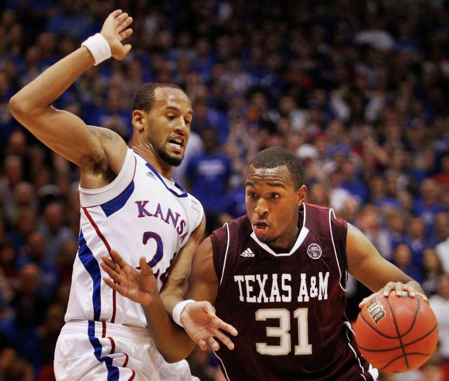 Texas A&M guard Elston Turner (31) drives on Kansas guard Travis Releford (24) during the second half of an NCAA college basketball game in Lawrence, Kan., Monday, Jan. 23, 2012. Turner scored 24 points. Kansas defeated Texas A&M 64-54. (AP Photo/Orlin Wagner) Photo: Orlin Wagner, Associated Press / AP