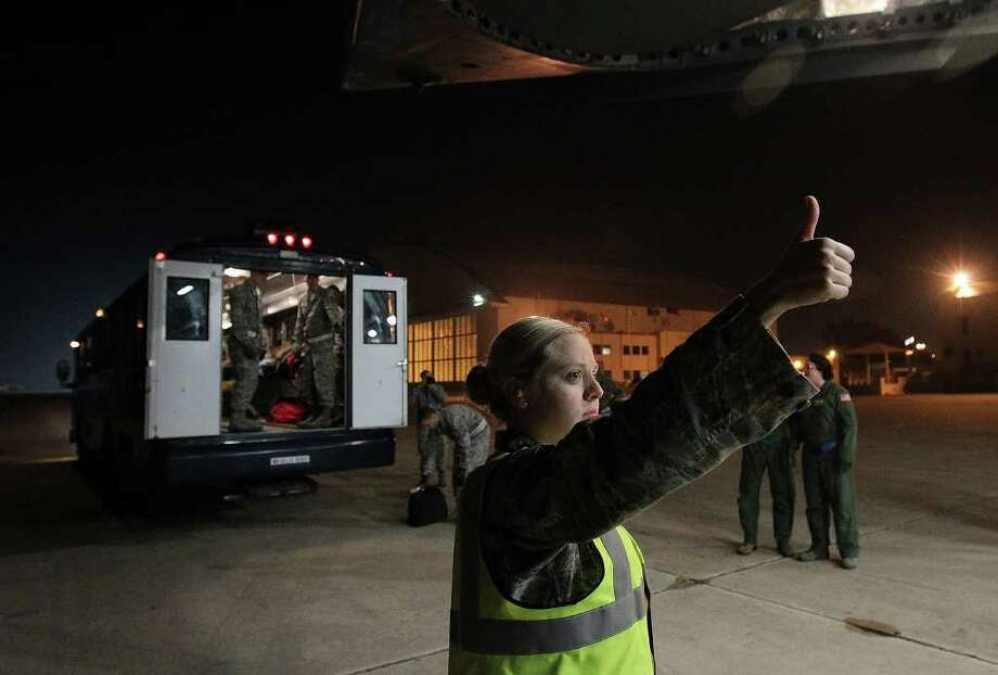Senior Airman Melissa Ball coordinates with air crew members who are transporting wounded soldiers from a C-17 aircraft to a bus on Friday. Ball is with the 559th Contingency Aeromedical Staging Facility at Wilford Hall Ambulatory Surgical Center. Photo: Kmhui@express-news.net, Kin Man Hui / San Antonio Express-News