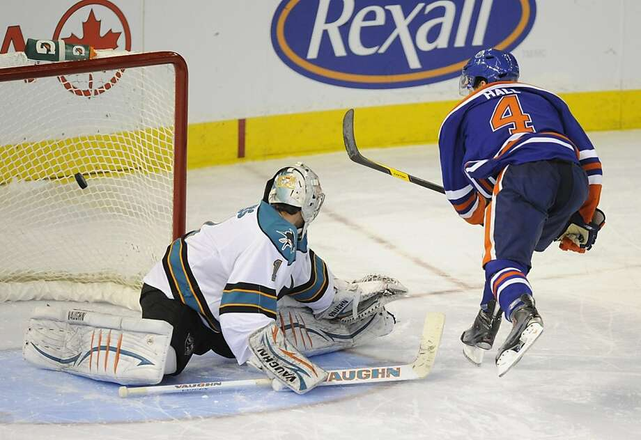 Edmonton Oilers' Taylor Hall, right, scores the winning shoot out goal on San Jose Sharks goalie Thomas Greiss during NHL hockey action in Edmonton on Monday, Jan. 23, 2012. (AP Photo/The Canadian Press, John Ulan) Photo: John Ulan, Associated Press