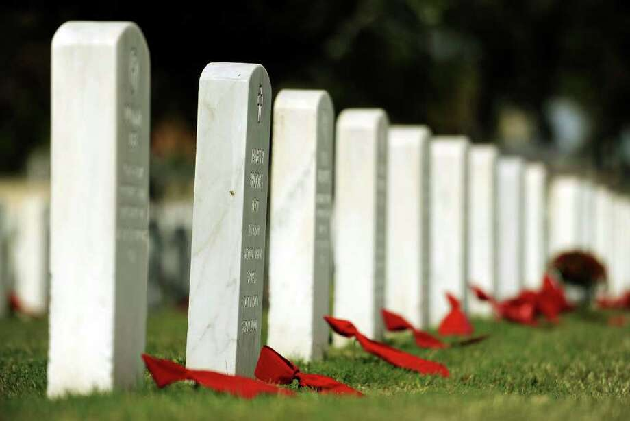 Red ribbons were placed on graves at Fort Sam Houston National Cemetery on Wednesday, Nov. 11, 2009. Veterans Day was once called Armistice Day, the day that the World War I ended in 1918. Photo: Gcalzada@express-news.net, Billy Calzada