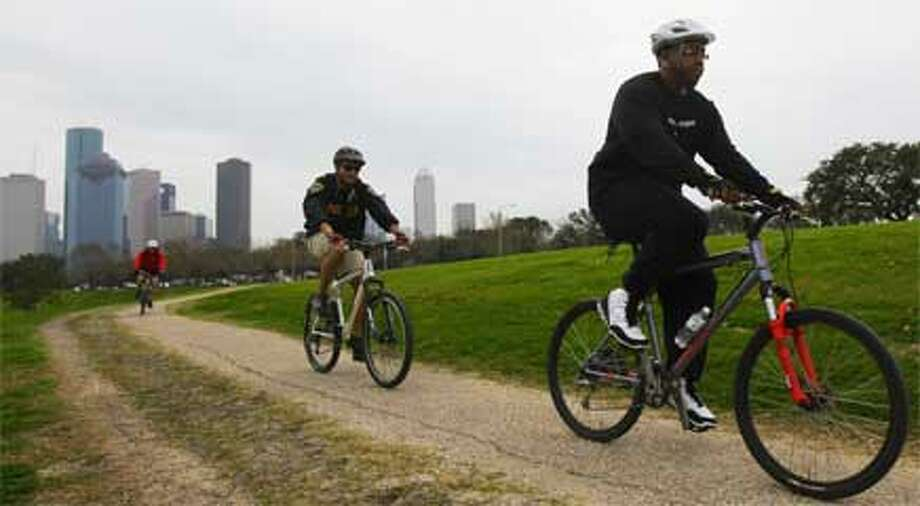 A group of cyclists ride a trail along Buffalo Bayou.