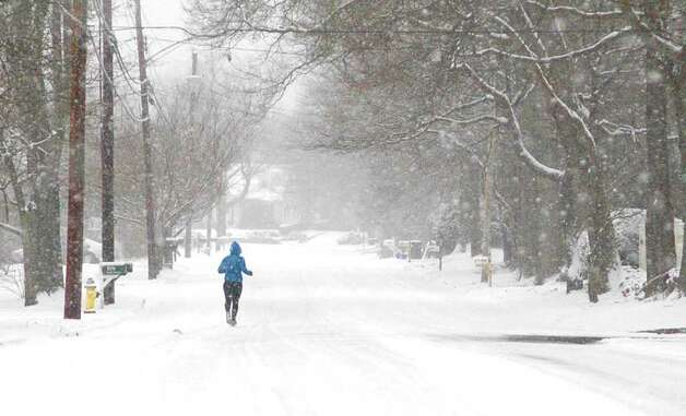 A jogger navigates the snowy streets of Fairfield on Saturday morning. Photo: Cathy Zuraw / Connecticut Post