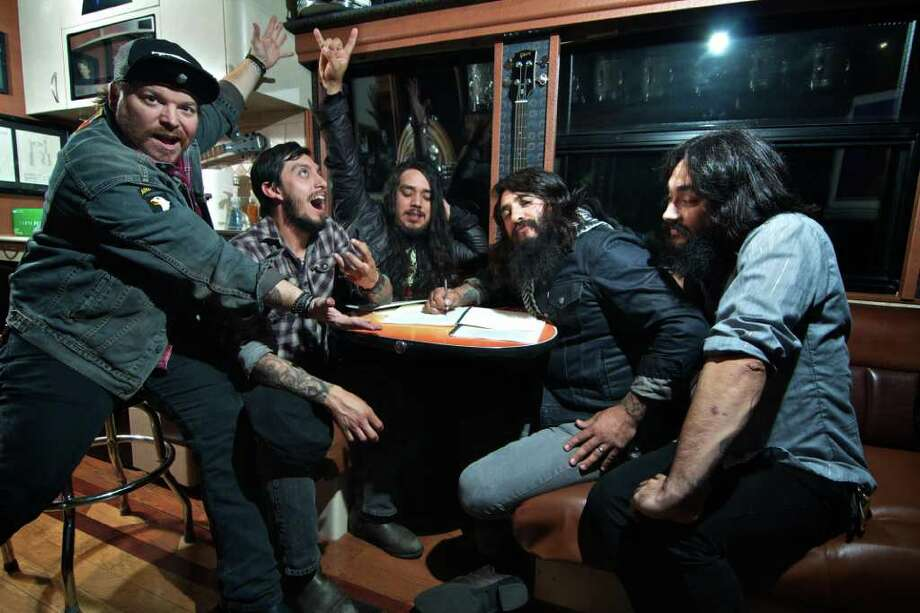Members of The Heroine - Guhly, from left, The Kidd, Johnny Lightning, Lynwood Presley King and DD - sign their contract with EMG on the Gibson tour bus. Photo: The Heroine