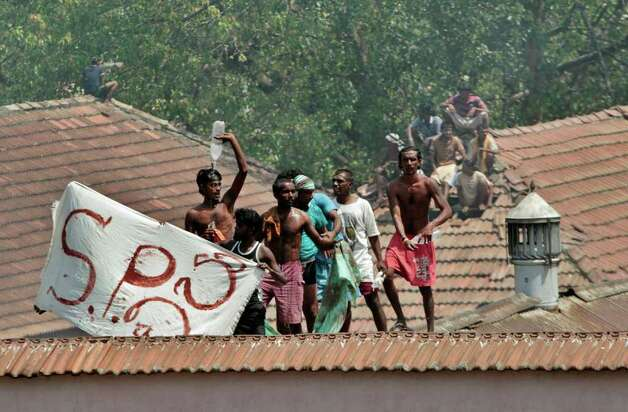 Sri Lankan prisoners climb onto neighboring buildings during a clash between prison guards and inmates in Colombo, Sri Lanka, on Tuesday. A clash between guards and inmates at a Sri Lankan prison on Tuesday has injured at least 21 people, officials said. They said the inmates began rioting to demand the replacement of the prison chief. Photo: AP