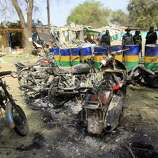 Police officers stand behind burned taxis  following last Friday's suicide bombing outside the state police headquarters in Kano, Nigeria, on Tuesday. Police said Tuesday that members of the radical Islamist group Boko Haram dressed in uniforms resembling those of soldiers and police officers when they launched their attack Friday in Kano.