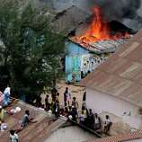 Sri Lankan prisoners climb onto neighboring buildings as a ward is seen set on fire in Colombo, Sri Lanka, on Tuesday. A clash between guards and inmates at a Sri Lankan prison broke on Tuesday after the inmates demanded the replacement of the prison chief, officials said.
