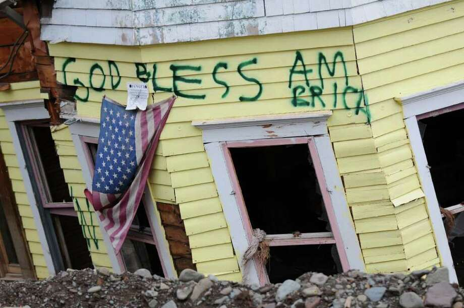 View of graffiti on a devastated home on Thursday Nov. 17, 2011 in Prattsville, NY, destroyed by flooding from Tropical Storm Irene. Lawmakers are looking a measure that would let localities float five year bonds to help pay for flood recovery in the wake of Hurricane Irene and Tropical Storm Lee. (Philip Kamrass / Times Union archive ) Photo: Philip Kamrass / 00015455A
