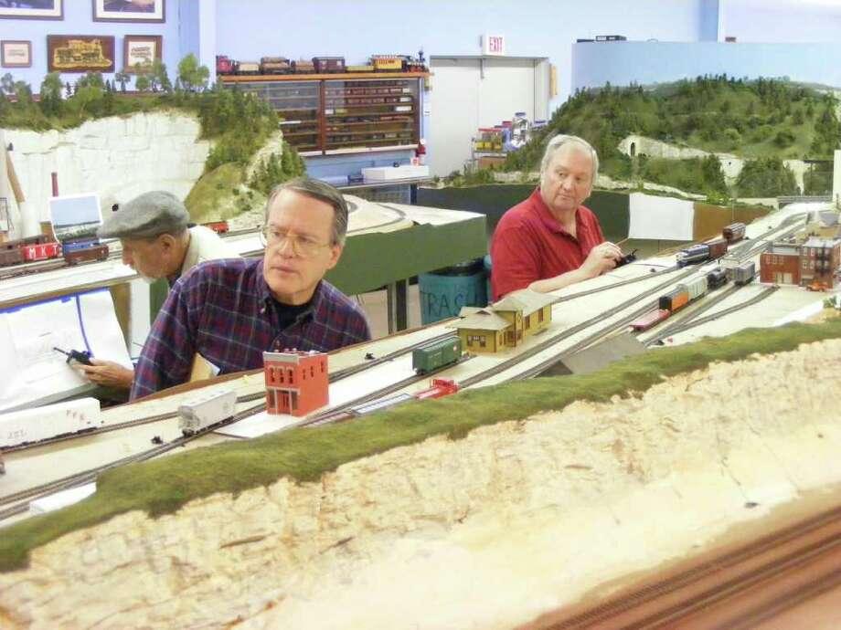 Chris Roehl, of Windcrest, left, and Gary Brown of San Antonio observe an approaching model train on tracks at the Bob Clark Rail Heritage Museum in Live Oak. Photo by Jeff B. Flinn Photo: Jeff B. Flinn / Northeast Herald