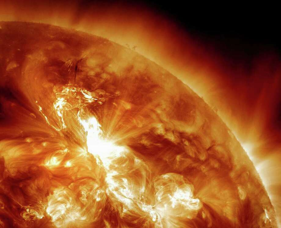 This handout image provided by NASA, taken Sunday night, Jan. 22, 2012, shows a  solar flare erupting on the Sun's northeastern hemisphere. Space weather officials say the strongest solar storm in more than six years is already bombarding Earth with radiation with more to come. The Space Weather Prediction Center in Colorado observed a flare Sunday night at 11 p.m. EST. Physicist Doug Biesecker said the biggest concern from the speedy eruption is the radiation, which arrived on Earth an hour later. It will likely continue through Wednesday. It's mostly an issue for astronauts' health and satellite disruptions. It can cause communication problems for airplanes that go over the poles. (AP Photo/NASA) Photo: Associated Press / NASA