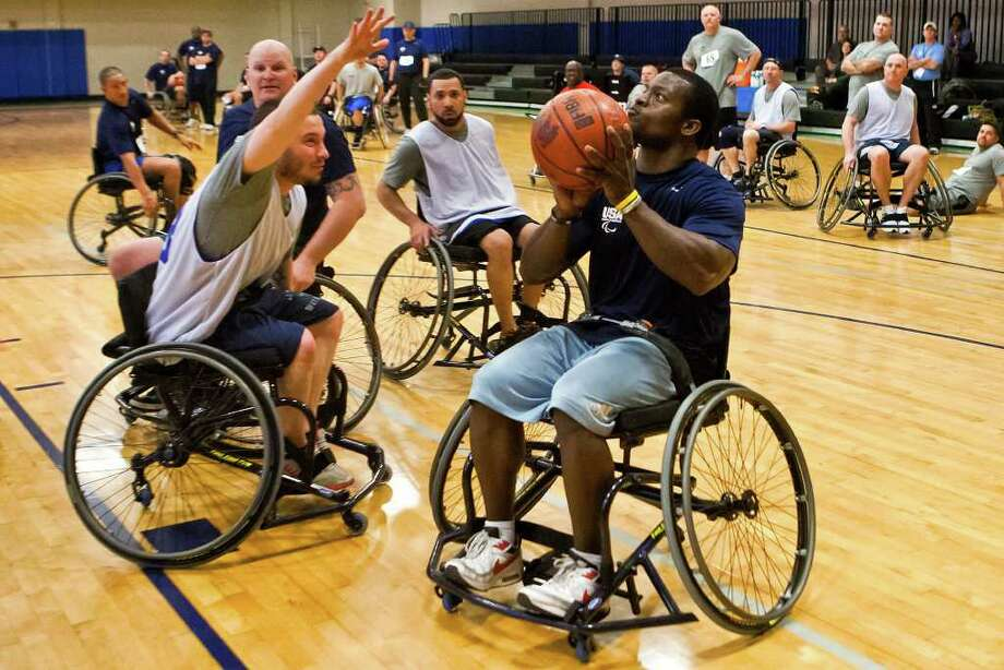 Zac Martinez, left, tries to block the shot of Matt Sanders during a wheelchair basketball game Friday at Randolph AFB, part of the inaugural five-day Adaptive Fitness & Sports Camp. Photo by Marvin Pfeiffer Photo: MARVIN PFEIFFER, Marvin Pfeiffer / Prime Time Newspapers / Prime Time Newspapers 2012