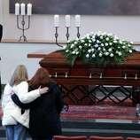 Two women pause to pay their respect in front of the casket of legendary Penn State football coach Joe Paterno during a viewing in the worship room of the Pasquerilla Spiritual Center on the Penn State University campus on Tuesday in State College, Pa. At left is current Penn State football player John Duckett.
