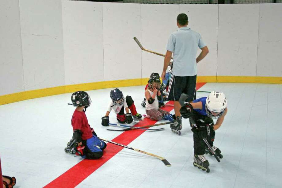 Teaching roller hockey to 5- and 6-year-olds focuses on the basics, such as learning to maintain balance and moving the puck. Photo: TOM BEHRENS