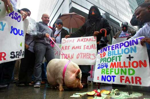 """Occupy Houston members along with members of Good Jobs Greater Houston protest outside of CenterPoint Energy Tuesday, Jan. 24, 2012, in Houston.  The pig represented the """"greedy, tax-dodging corporations,"""" according to Good Jobs Greater Houston organizer Jimmie Brown said. Photo: Cody Duty, Houston Chronicle / © 2011 Houston Chronicle"""