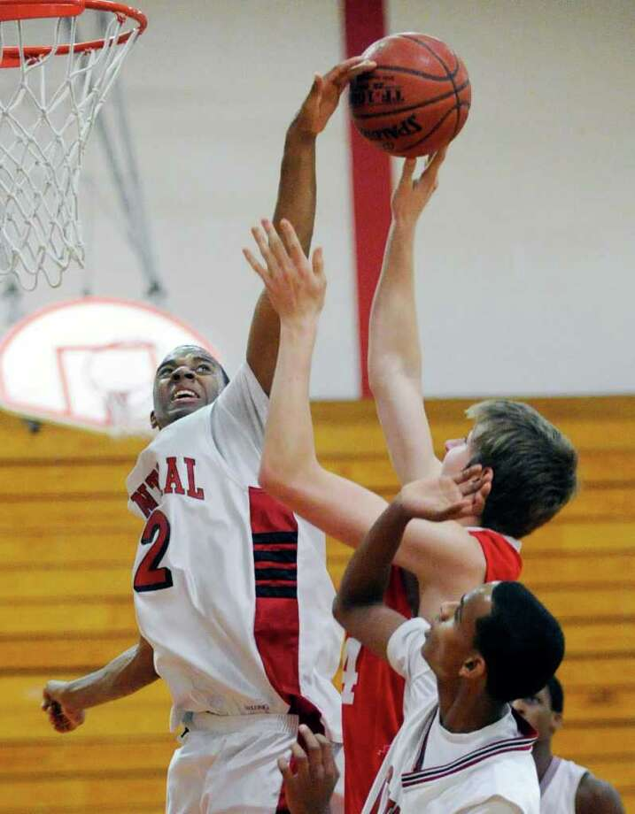 At left, Josh Wilkerson # 12 of Central High School rejects the shot of Sem Kroon of Greenwich High School during boys high school basketball game between Greenwich High School and Central High School of Bridgeport at Central, Tuesday night, Jan. 24, 2012 Photo: Bob Luckey / Greenwich Time