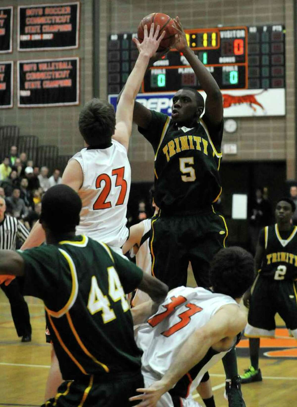 Trinity's Brandon Wheeler tries to shoot over Ridgefield's Patrick Racy during their game at Ridgefield High School on Tuesday, Jan. 24, 2012.