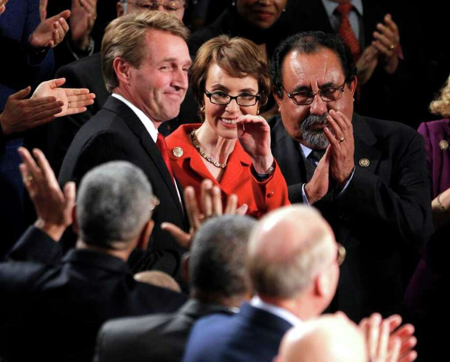 Retiring Rep. Gabrielle Giffords, D-Ariz., flanked by Rep. Jeff Flake, R-Ariz., left, and Rep. Raul Grijalva, D-Ariz., on Capitol Hill in Washington. Photo: Pablo Martinez Monsivais, Associated Press / AP
