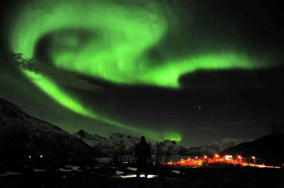 The aurora borealis, or Northern Lights, are seen near the city of Tromsoe, northern Norway, late Tuesday, Jan. 24, 2012. Stargazers were out in force in northern Europe on Tuesday, hoping to be awed by a spectacular showing of northern lights after the most powerful solar storm in six years. (AP Photo/Scanpix Norway, Rune Stoltz Bertinussen) Photo: Rune Stoltz Bertinussen, AP / AP2012