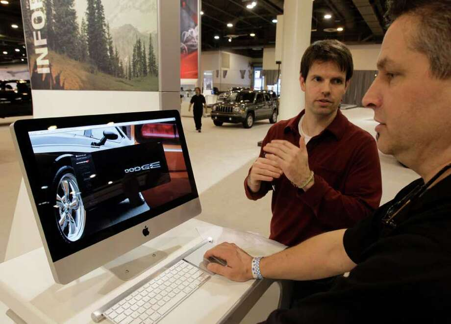 Marc Graziani, left, and Chris Pipitonet, both from Detroit, work on an interactive display Tuesday in the Chrysler, Jeep, Dodge and Fiat display area for the 2012 Houston Auto Show at Reliant Center. Technology can help car shoppers see more at the show. Photo: Melissa Phillip / © 2011 Houston Chronicle