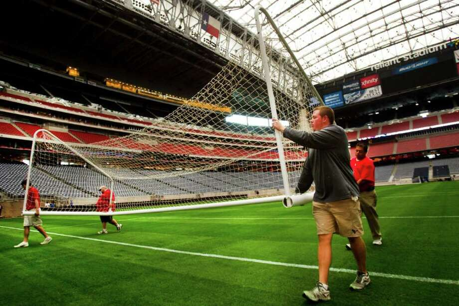 Jared Davis, in gray, of the Reliant Stadium grounds crew, carries a goal with Daniel Ryan, far left, Shane Robertson, left center, and Mario Garcia, far right, while preparing the stadium for an international soccer match between Mexico and Venezuela. Photo: Brett Coomer, Houston Chronicle / © 2012 Houston Chronicle