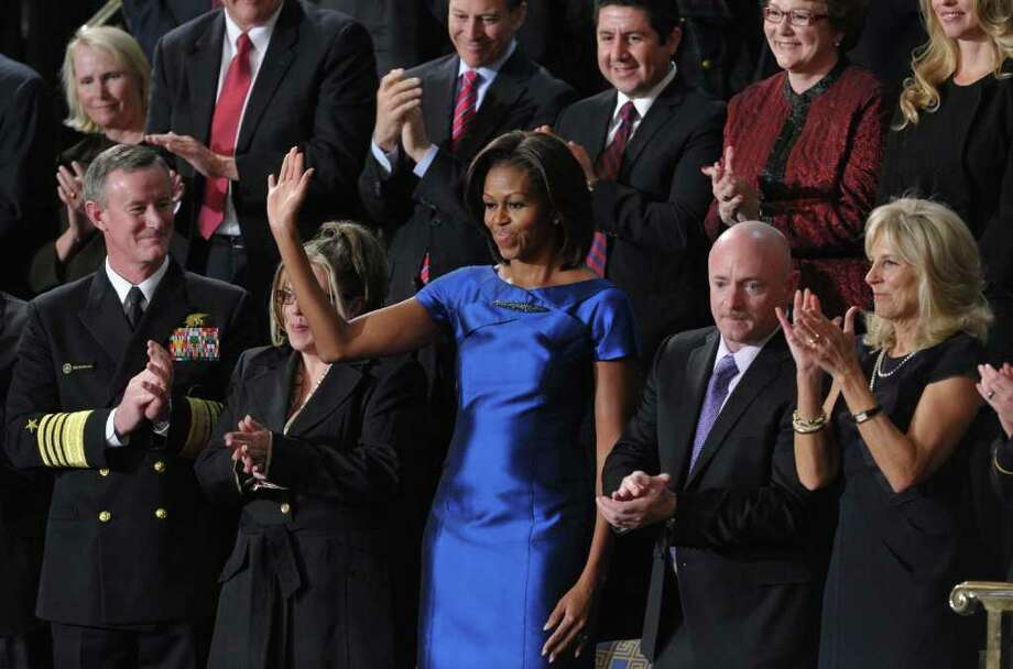 First lady Michelle Obama waves from the House gallery prior to President Barack Obama's State of the Union address Tuesday night. At her left is astronaut Mark Kelly, husband of U.S Rep. Gabrielle Giffords. Photo: MANDEL NGAN / AFP