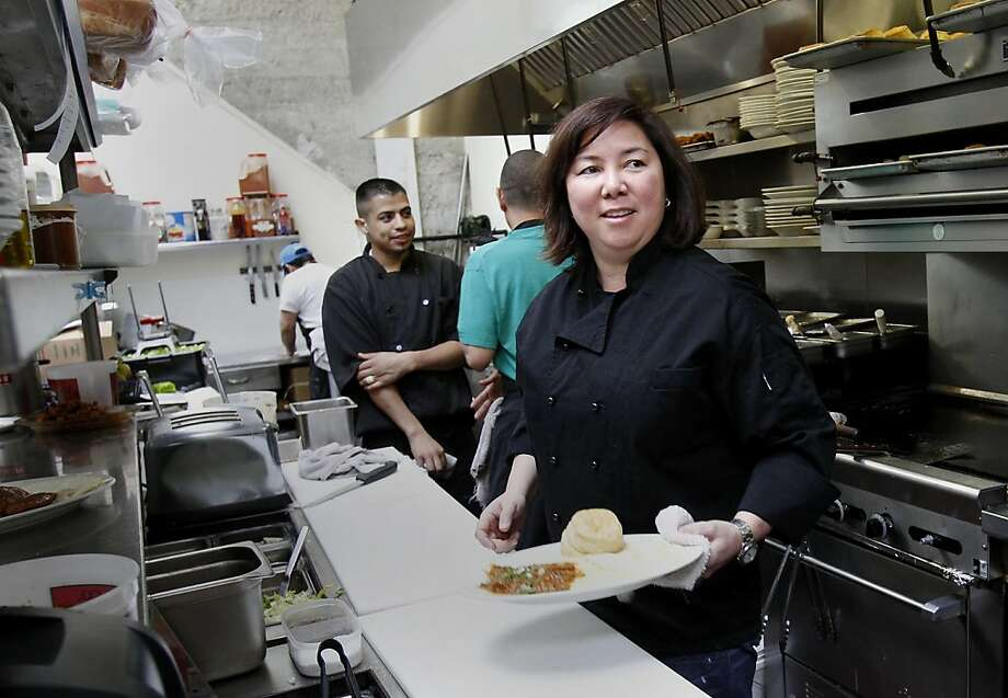 Brenda Buenviaje, owner of Brenda's, worked in the kitchen after the press conference.  She may take advantage of the new loan program and has benefitted from previous city loans. San Francisco Mayor Ed Lee announced a new loan program for small businesses in the city at the popular restaurant called Brenda's on Polk Street. Photo: Brant Ward, The Chronicle