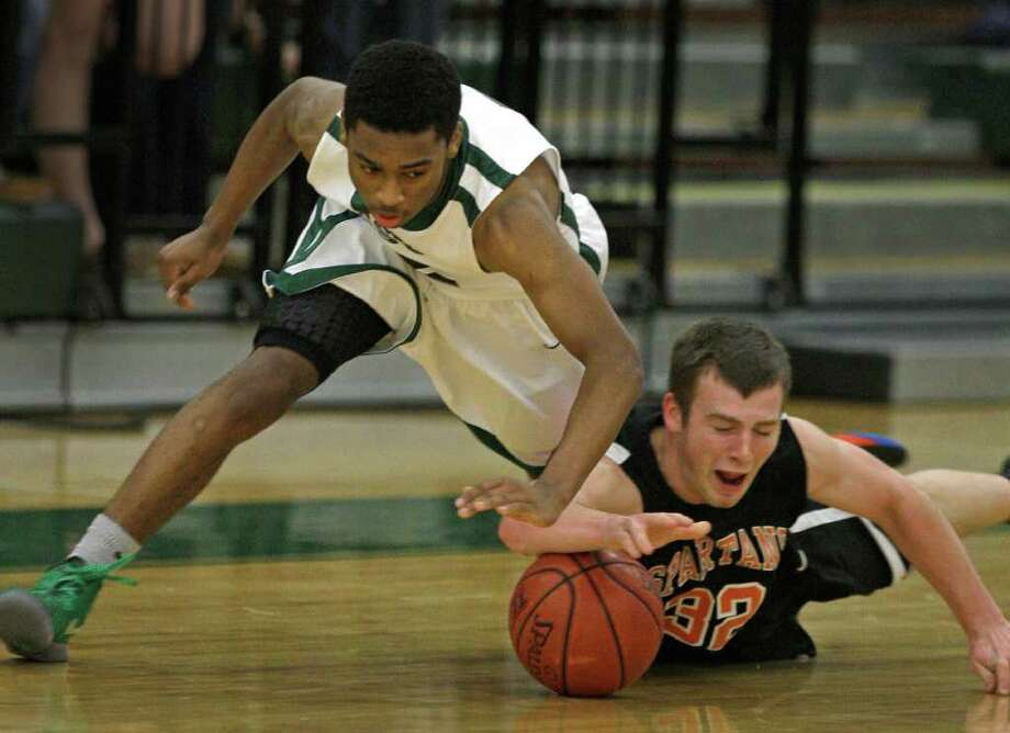 Strake Jesuit's John Gillon, left, and Seven Lakes' Connor Coleman engage in an intense scramble. Photo: Melissa Phillip / © 2011 Houston Chronicle