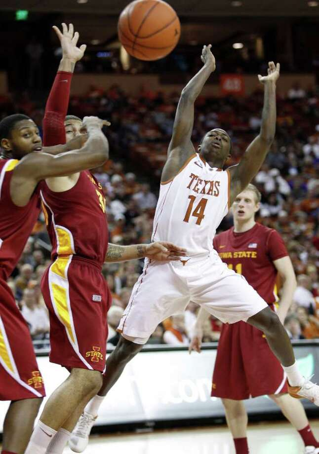 Texas' J'Covan Brown (14) is fouled as he drives to the basket against Iowa State's Melvin Ejim, left, and Royce White, center, during the second half of an NCAA college basketball game, Tuesday, Jan. 24, 2012, in Austin. Photo: Eric Gay, Associated Press