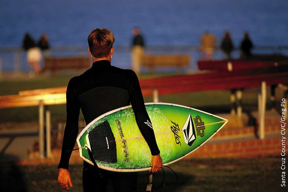 A surfer carries his board at Lighthouse Point in Santa Cruz, not far from where three Hawaiian student princes are said to have introduced the sport in 1885. Photo: Santa Cruz County CVC, Greg Pio