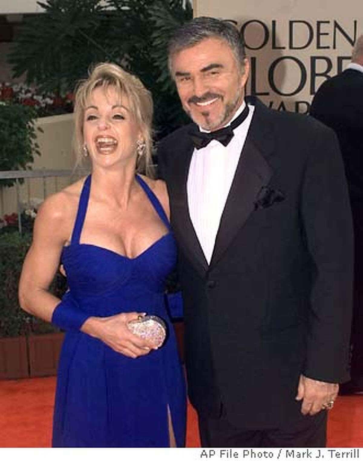** FILE ** Burt Reynolds and Pam Seals arrive at the annual Golden Globe Awards in Beverly Hills, Calif., Jan. 18, 1998. Reynolds sued his former girlfriend Monday, Nov. 8, 2004, in West Palm Beach, Fla. Reynolds alleges Pamela Seals was threatening to falsely accuse him of abuse if he did not pay millions of dollars in extortion. (AP Photo/Mark J. Terrill, File)