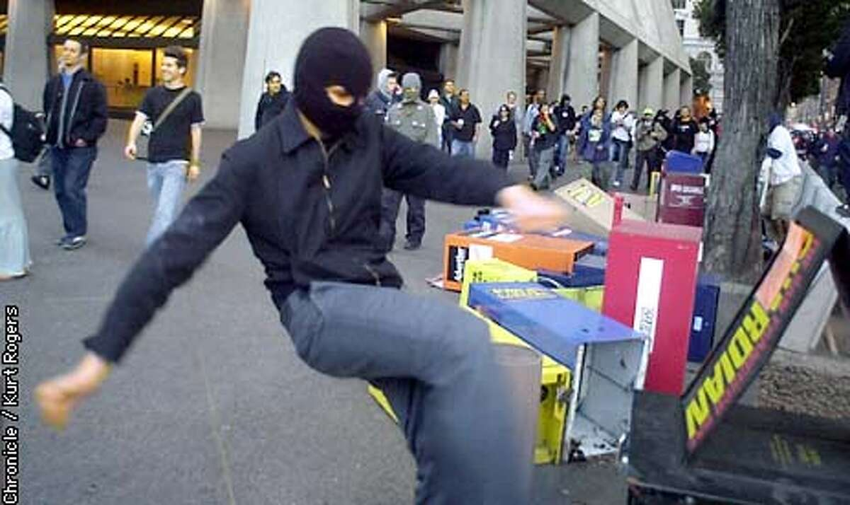 A protester kiks over news stands in front of the Transameica building. Protesters ran up and down the streets of San Francisco after the peace ralley .Photo By Kurt Rogers