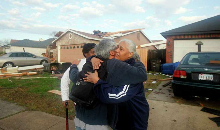 Freeda Mosley, right, hugs neighbor Antonio Matias after a storm swept through their neighborhood in northwest San Antonio, Texas early Wednesday, Jan. 25, 2012. The storm damaged several homes in the area and tore the roof off of a home on the 8900 block of Deer Park. Standing behind Mosley and Matias is Mary Wilson. (AP Photo/San Antonio Express-News)  MAGS OUT, RUMBO DE SAN ANTONIO OUT, NO SALES,  MANDATORY CREDIT Photo: JOHN DAVENPORT, Associated Press / SAN ANTONIO EXPRESS-NEWS