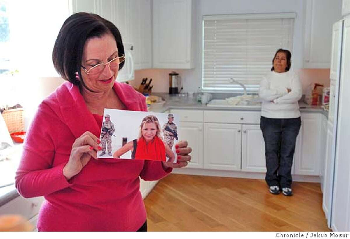 Nancy Ruzicka holds a photo of her daughter Marla Ruzicka, 28, who died in a car bomb attack in Iraq, as family friend Carman Errdondo stands in the background. Event on 4/18/05 in Lakeport. JAKUB MOSUR / The Chronicle