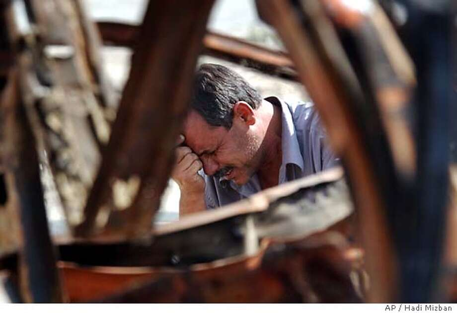 A man cries for his slain son next to a charred civilian vehicle which was blown up when insurgents set off a car bomb targeting a U.S. convoy in Baghdad, Iraq Thursday, Oct. 28, 2004. The man's son was driving the civilian car which was destroyed as collateral damage when the bomb, aimed at US forces, exploded. (AP Photo/Hadi Mizban) Photo: HADI MIZBAN